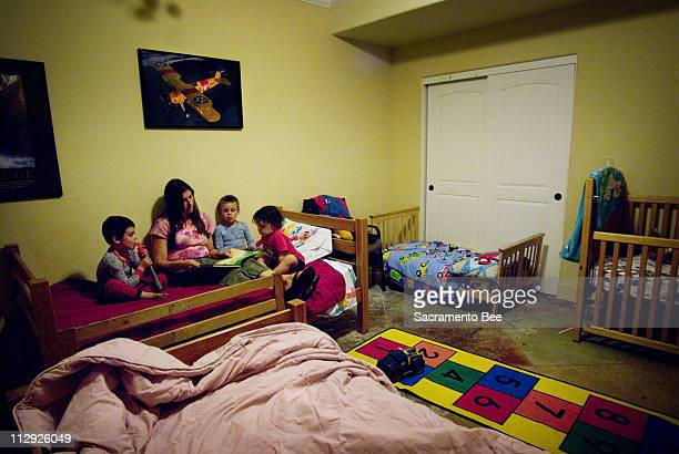 Lynne Cimorelli center reads a bedtime story to her youngest children from left Nicholas Christian and Joey at their El Dorado Hills home August 21...