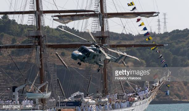 Lynx helicopter flies by Portuguese Navy tall ship and school ship NRP Sagres laying at anchor in Tagus River during the commemoration of the 100th...
