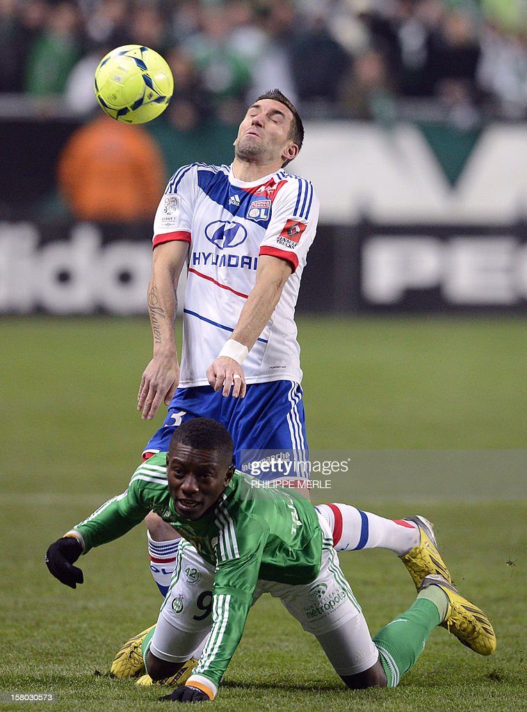 Lyon forward Anthony Reveillere (back) fights for the ball with Saint-Etienne's Ivorian midfielder Max Alain Gradel on December 9, 2012 during a French L1 football match at the Geoffroy-Guichard stadium in the central city of Saint-Etienne. MERLE