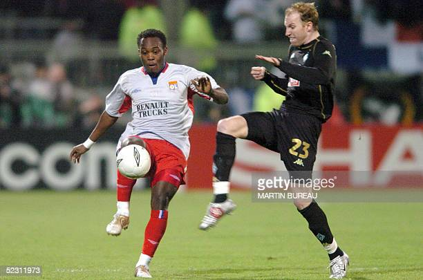 Lyon's Ghanaian midfielder Michael Essien fights for the ball with Bremen Swiss midfielder Ludovic Magnin 08 March 2005 at the Gerland Stadium in...