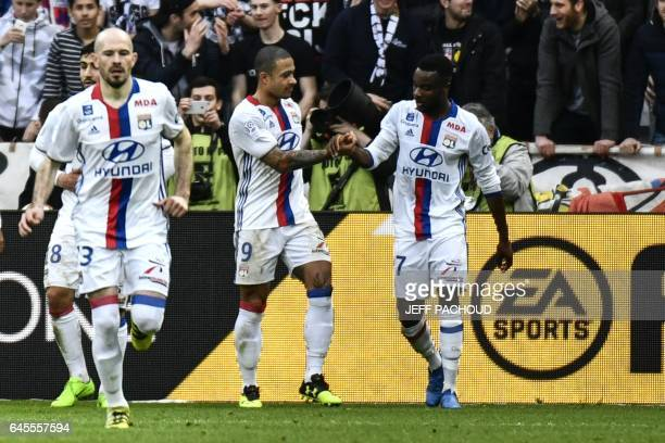 Lyon players celebrate after Lyon's Dutch forward Memphis Depay scored a goal during the French L1 football match Olympique Lyonnais vs FC Metz at...
