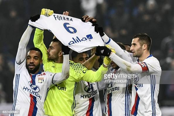 TOPSHOT Lyon players celebrate and pay tribute to Gueida Fofana after Lyon's French forward Mathieu Valbuena scored a goal during the French L1...