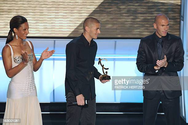 Lyon striker Karim Benzema poses after receiving the best player of the French League 1 trophy from former football player Zinedine Zidane and French...