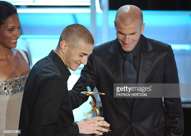 Lyon striker Karim Benzema receives the best player of the French League 1 trophy from former football player Zinedine Zidane and French sprinter...