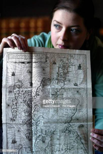 Lyon Turnbull staff member Alex Dove with the Nicolay Rutter map an ancient map of Scotland which is on display ahead of going up for auction at Lyon...