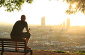 Man on a bench relaxing, checking his phone and enjoying the summer sunrise over the city of Lyon, France.