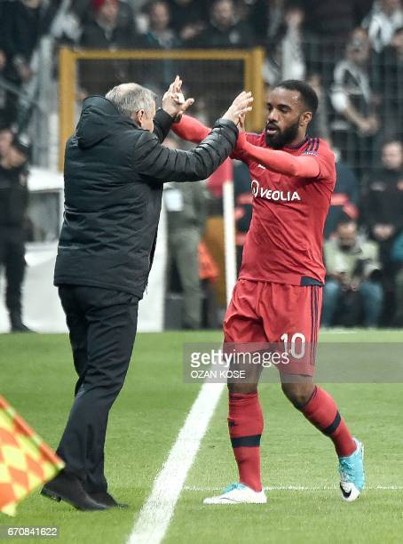 Lyon's Alexandre Lacazette celebrates with head coach Bruno Genesio during the UEFA Europa League second leg quarter final football match between...