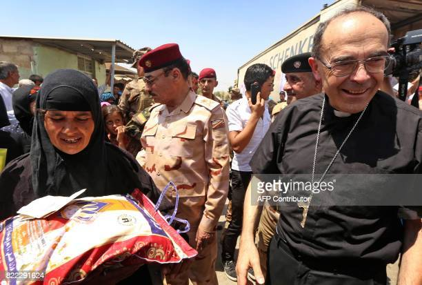 Lyon's Archbishop Cardinal Philippe Barbarin distributes food aid to an Iraqi woman as he visits east Mosul on July 25 2017 Barbarin hailed the...