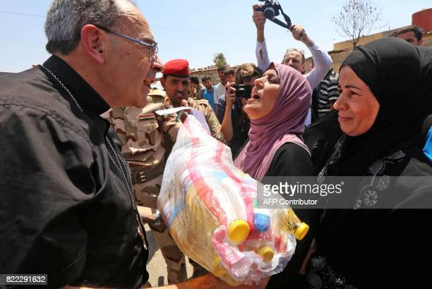 Lyon's Archbishop Cardinal Philippe Barbarin distributes food aid to Iraqi women as he visits east Mosul on July 25 2017 Barbarin hailed the...