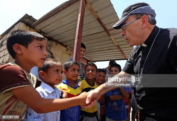 Lyon's Archbishop Cardinal Philippe Barbarin greets Iraqi children as he visits east Mosul on July 25 2017 Barbarin hailed the 'rebirth' of Iraq's...
