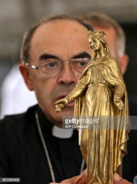 Lyon's Archbishop Cardinal Philippe Barbarin holds a statue of Virgin Mary during a visit to the church of the Holy Spirit in east Mosul on July 25...