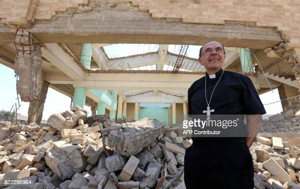 Lyon's Archbishop Cardinal Philippe Barbarin walks amid the rubble of the Martyr's church as he visits east Mosul on July 25 2017 Barbarin hailed the...