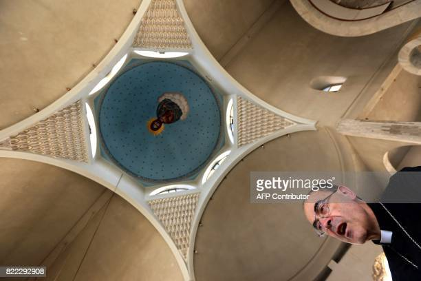Lyon's Archbishop Cardinal Philippe Barbarin walks inside the builiding of Saint Ephraim's Cathedral as he visits east Mosul on July 25 2017 Barbarin...