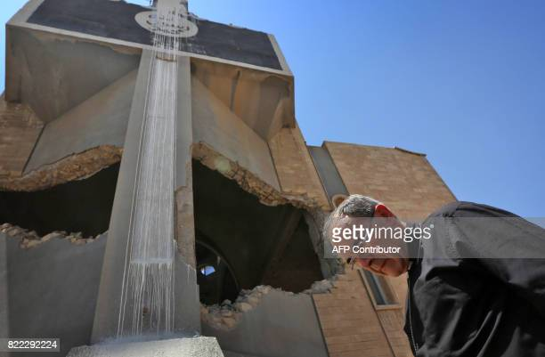 Lyon's Archbishop Cardinal Philippe Barbarin walks next to the damaged builiding of Saint Ephraim's Cathedral as he visits east Mosul on July 25 2017...