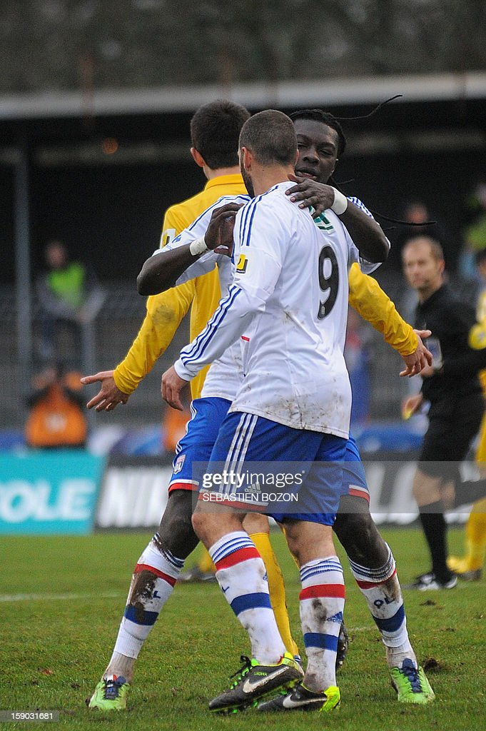 Lyon's Argentinian forward Lisandro Lopez (C) is congratulated by Lyon's French forward Bafetimbi Gomis (R) after scoring a goal during their French cup football match Epinal (SAS) versus Lyon (OL) at the Colombiere Stadium in Epinal, on January 6, 2013.