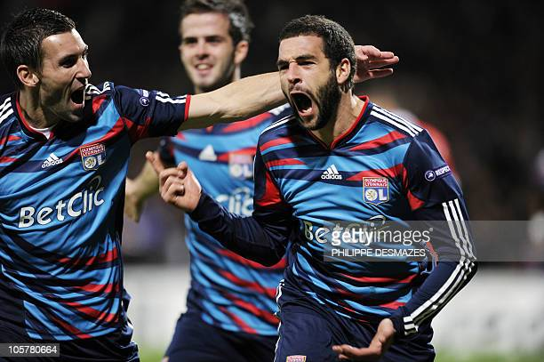 Lyon's Argentinian forward Lisandro Lopez is congratuled by his teamates French defender Anthony Reveilliere and Bosnian midfielder Miralem Pjanic...