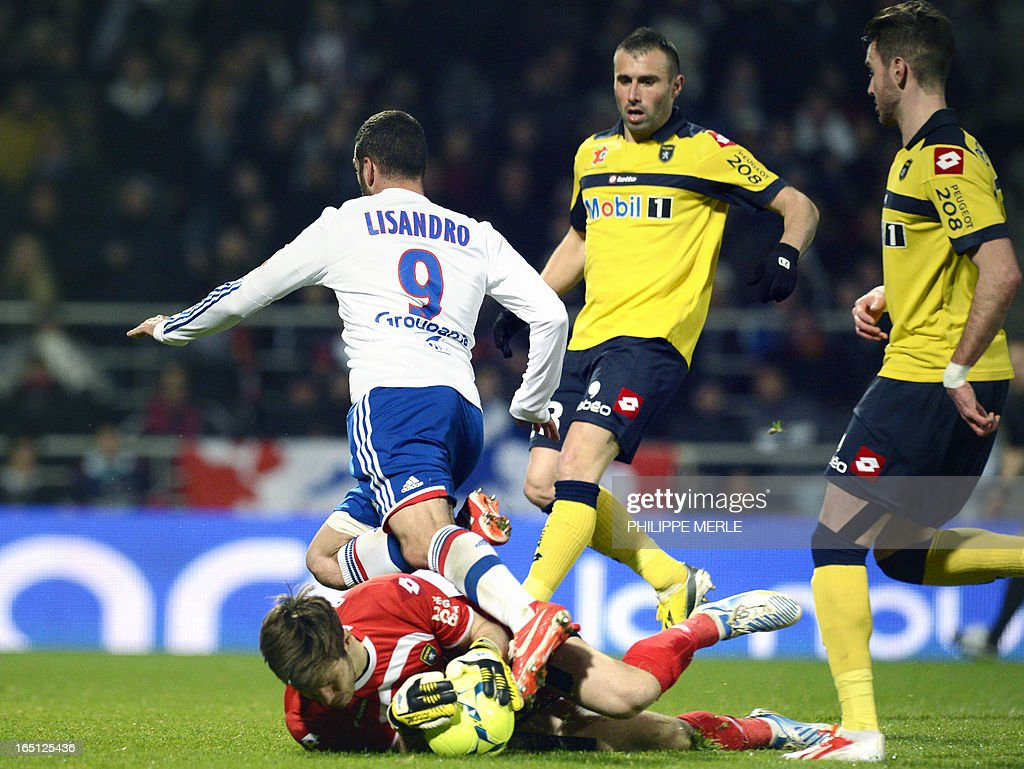 Lyon's Argentinian forward Lisandro Lopez (C) vies with Sochaux' French goalkeeper Simon Pouplin (L) during the French L1 football match Lyon vs Sochaux on March 31, 2013 at the Gerland stadium in Lyon. MERLE