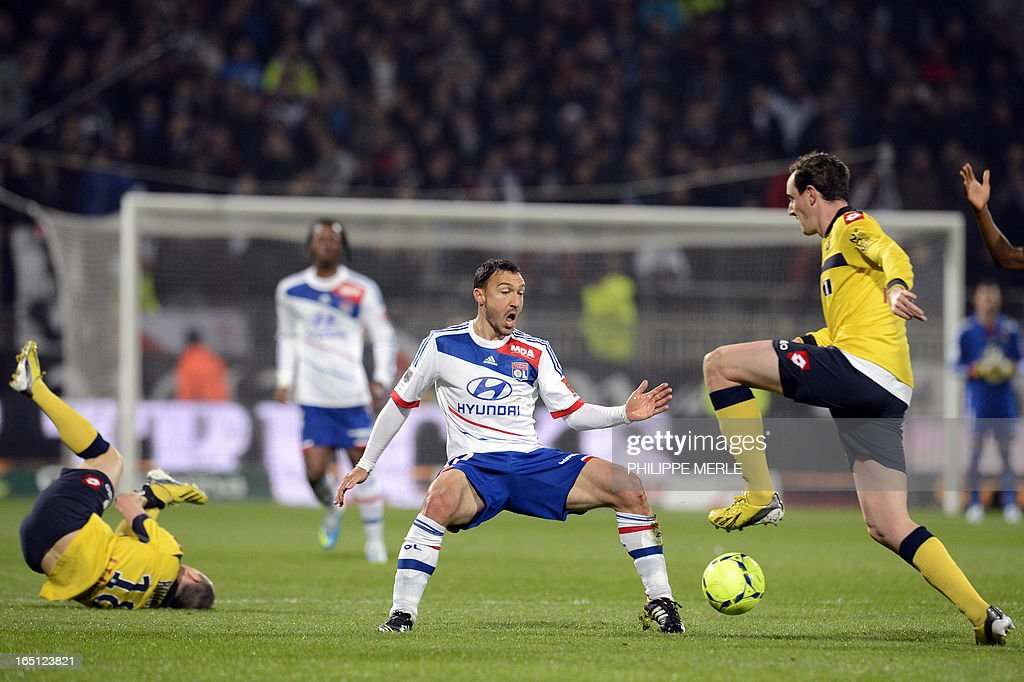 Lyon's Belgian midfielder Steed Malbranque (C) vies for the ball with Sochaux' French midfielder Sebastien Roudet (L) and Sochaux' French midfielder Loic Poujol (R) during the French L1 football match Lyon vs Sochaux on March 31, 2013 at the Gerland stadium in Lyon.