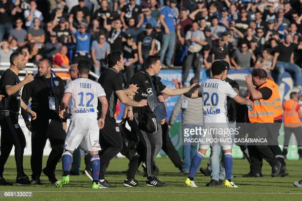 Lyon's Brazilian defender Rafael da Silva and Lyon's midfielder Jordan Ferri talk with Lyon's staff on the pitch after scuffles erupted at halftime...