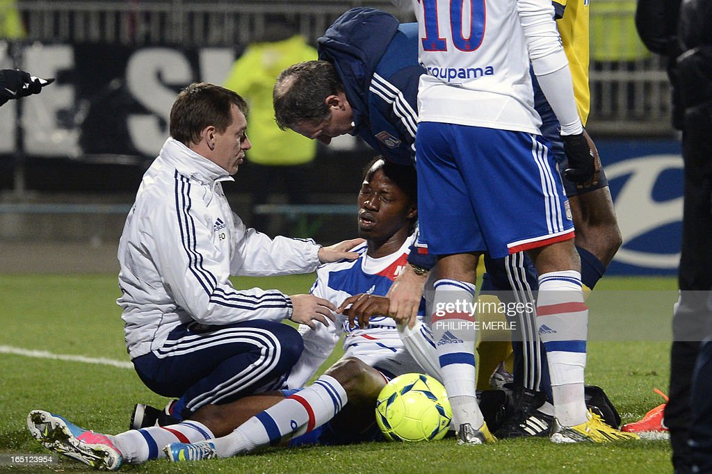 Lyon's Burkinabe defender Bakary Kone (C) receives medical treatment during the French L1 football match Lyon vs Sochaux on March 31, 2013 at the Gerland stadium in Lyon.