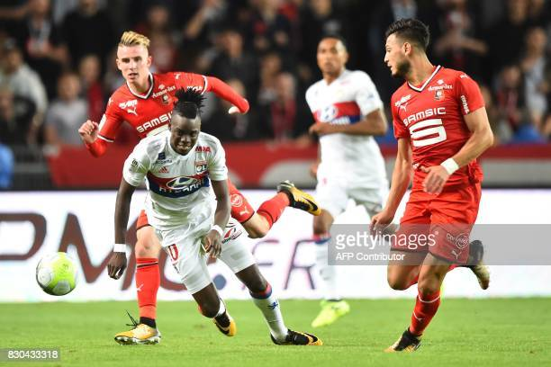 Lyon's Burkinabe forward Bertrand Traore vies for the ball with Rennes' French midfielder Benjamin Bourigeaud and Rennes' Algerian defender Rami Amir...