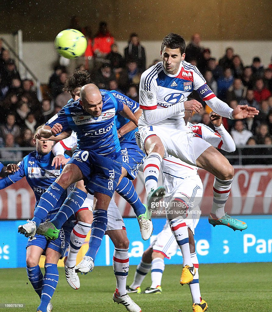Lyon's captain Maxime Gonalons (R) heads and scores a goal next to Troyes' forward Benjamin Nivet (L) during the French L1 football match Troyes vs Lyon on January 12, 2013 at the Aube Stadium in Troyes, northern France. PHOTO