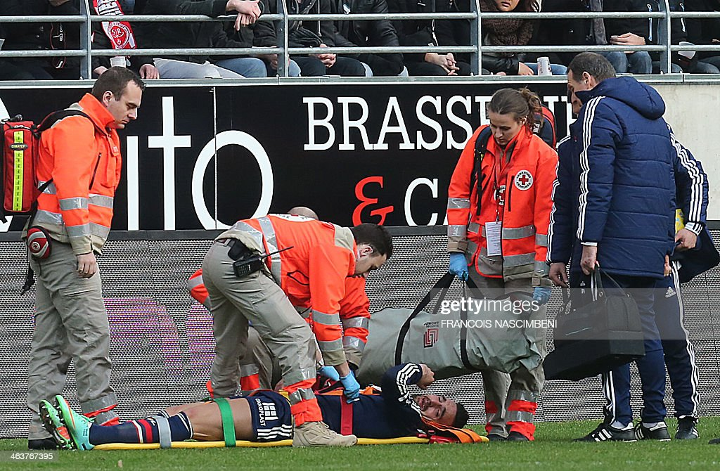 Lyon's defender Miguel Lopes lies on a stretcher after being injured during a French L1 Football match between Reims and Lyon on January 19, 2014 at the Auguste Delaune Stadium in Reims.