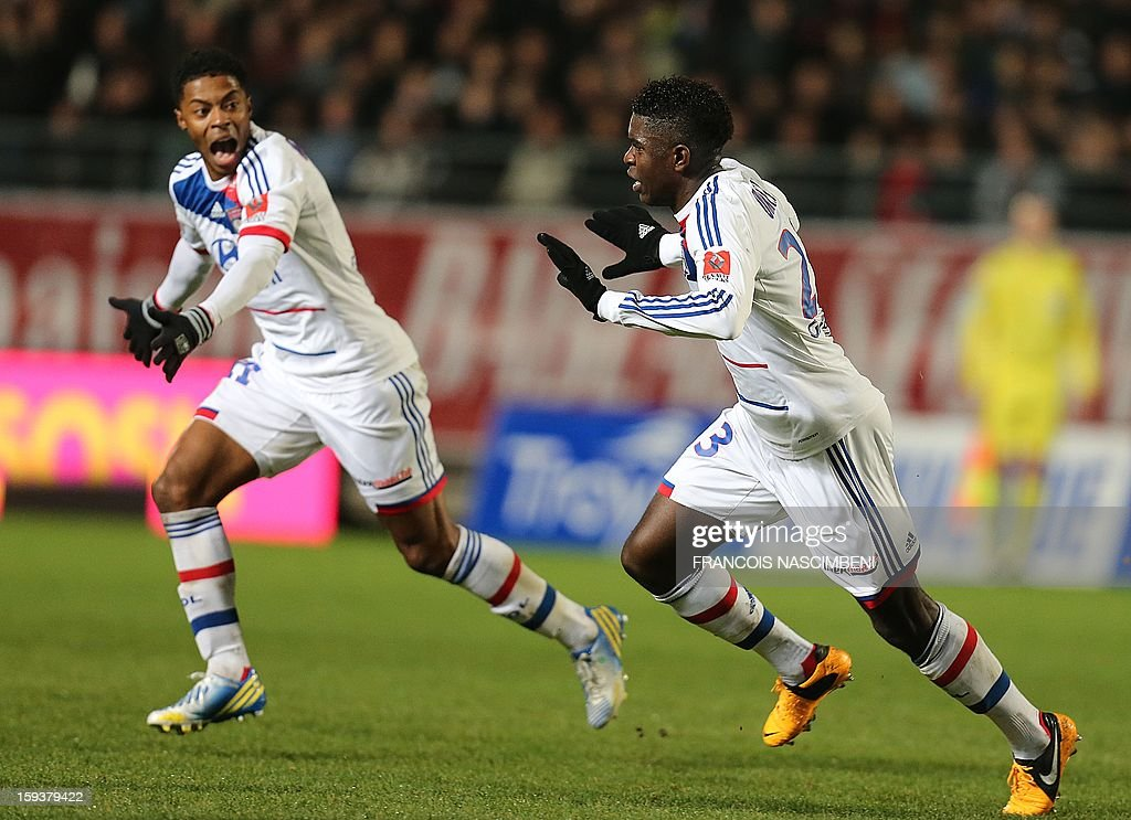 Lyon's defender Samuel Um Titi (R) celebrates after scoring a goal during a French L1 football match between Troyes and Lyon on January 12, 2013 at the Aube Stadium in Troyes.