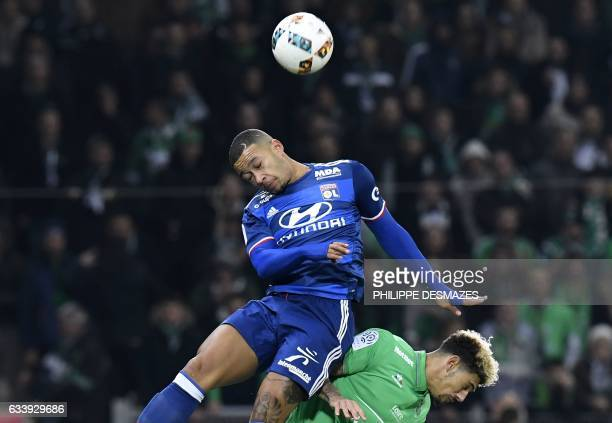 Lyon's Dutch forward Memphis Depay heads the ball next to SaintEtienne's French defender Kevin Malcuit during the French L1 football match between AS...