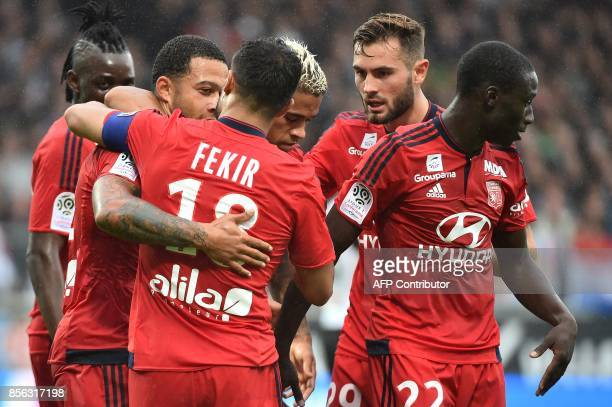 Lyon's Dutch forward Memphis Depay is congratulated by teammates Nabil Fekir Lucas Tousart and Kenny Tete during the French L1 football match between...