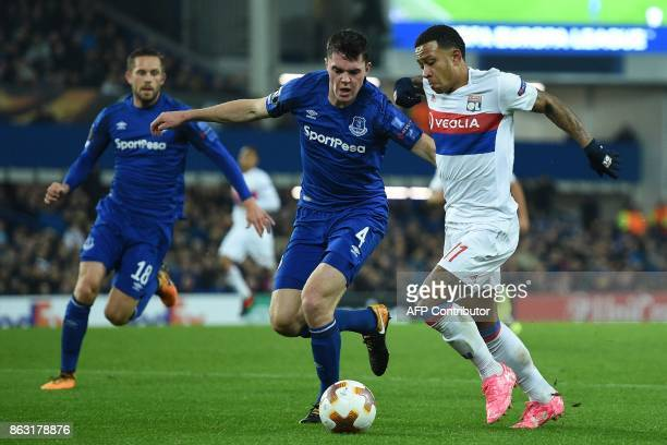 Lyon's Dutch striker Memphis Depay vies with Everton's English defender Michael Keane during the UEFA Europa League Group E match between Everton and...