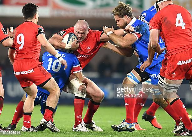 Lyon's English flanker Carl Fearns vies with Montpellier's South African flyhalf Demetri Catrakilis and Montpellier's South African flanker Wiann...