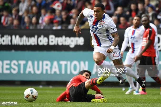 Lyon's forward Memphis Depay avoids the tackle from with Rennes' French midfielder Benjamin Andre during the French L1 football match between Rennes...