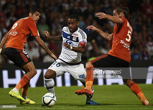 Lyon's Frecnh forward Alexandre Lacazette vies with Lorient's French defender Francois Bellugou and Lorient's French midfielder Medhi MostefaSba...