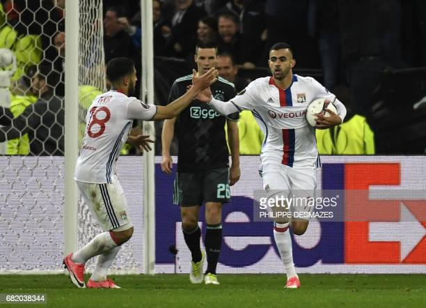 Lyon's French Algerian midfielder Rachid Ghezzal is congratuled by teammate Lyon's French midfielder Nabil Fekir after scoring a goal during the UEFA...