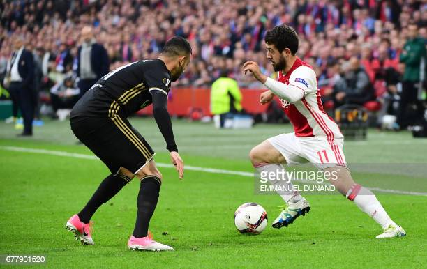 Lyon's French Algerian midfielder Rachid Ghezzal vies with Ajax forward Amin Younes vie during UEFA Europa League semifinal first leg Ajax Amsterdam...