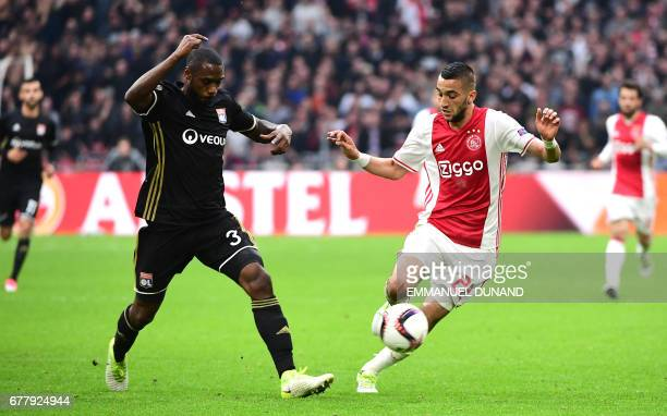 Lyon's French Cameroonian defender Nicolas Nkoulou vies with Ajax midfielder Hakim Ziyech during UEFA Europa League semifinal first leg Ajax...