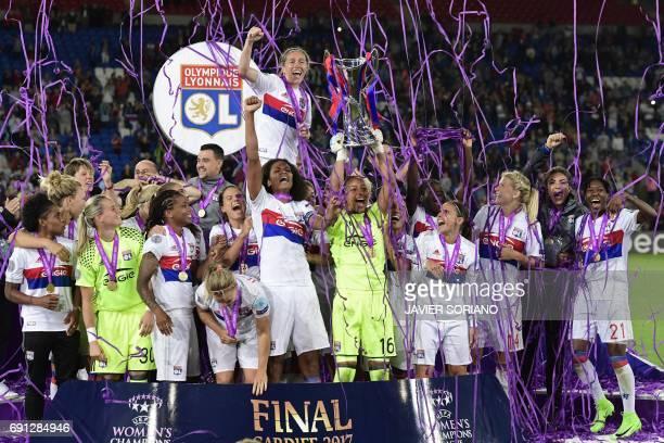 TOPSHOT Lyon's French captain Wendie Renard gestures as Lyon's French goalkeeper Sarah Bouhaddi holds aloft the Women's Champion's League trophy as...