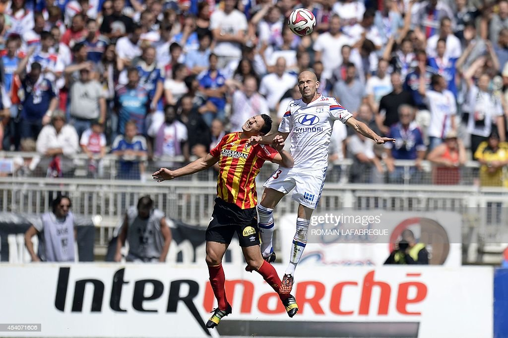 Lyon's French defender Christophe Jallet (R) jumps for the ball next to Lens' French forward Yohann Touzghar during the French L1 football match between Lyon (OL) and Lens (RCL) at the Gerland stadium in Lyon, central-eastern France, on August 24, 2014. AFP PHOTO / ROMAIN LAFABREGUE