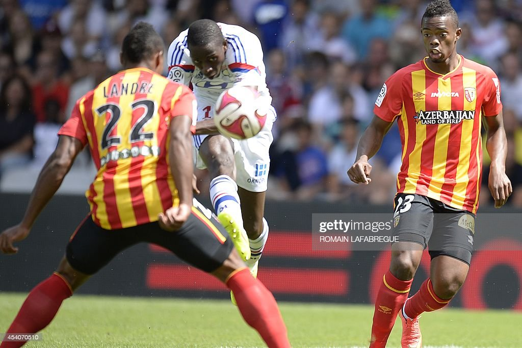 Lyon's French defender Mouhamadou Dabo (C) shoots the ball beetween Lens' French defender Loic Landre (L) and Lens' French midfielder Wylan Cyprien (R) during the French L1 football match between Lyon (OL) against Lens (RCL) at the Gerland stadium in Lyon, central-eastern France, on August 24, 2014. AFP PHOTO / ROMAIN LAFABREGUE