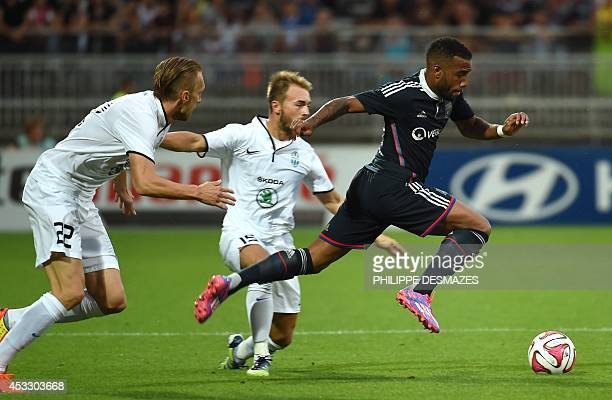 Lyon's French forward Alexandre Lacazette advances with the ball past Mlada Boleslav's Czech defender Antonin Rosa and Czech midfielder Jan Stohanzl...