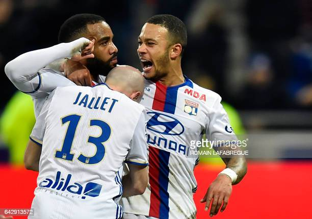 Lyon's French forward Alexandre Lacazette celebrates after scoring a goal with teammates Lyon's French defender Christophe Jallet and Lyon's Dutch...