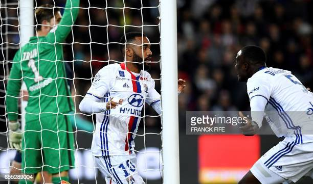 Lyon's French forward Alexandre Lacazette celebrates opening the scoring next to Lyon's defender Mouctar Diakhaby during the French L1 football match...
