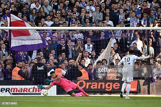 Lyon's French forward Alexandre Lacazette celebrates scoring a penalty goal during past Toulouse's French goalkeeper Alban Lafont during the French...