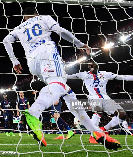 Lyon's French forward Alexandre Lacazette celebrates with teammate Lyon's defender Mouctar Diakhaby after scoring the opening goal during the French...