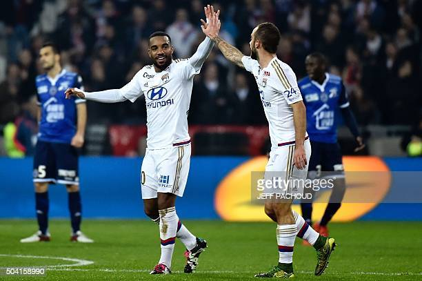 Lyon's French forward Alexandre Lacazette celebrates with teammates after scoring a goal during the French L1 football match between Olympique...