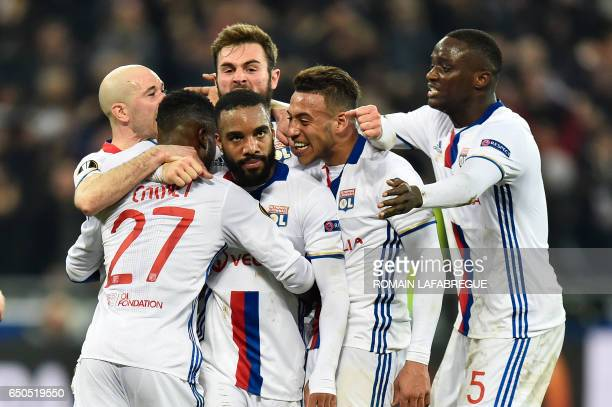 Lyon's French forward Alexandre Lacazette celebrates with teammates after scoring a goal during the UEFA Europa League round of 16 football match...
