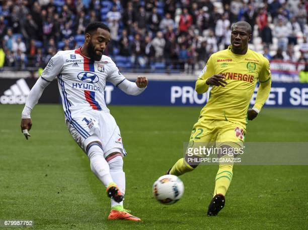Lyon's French forward Alexandre Lacazette challenges Nantes' French midfielder Abdoulaye Toure during the French L1 football match between Lyon and...