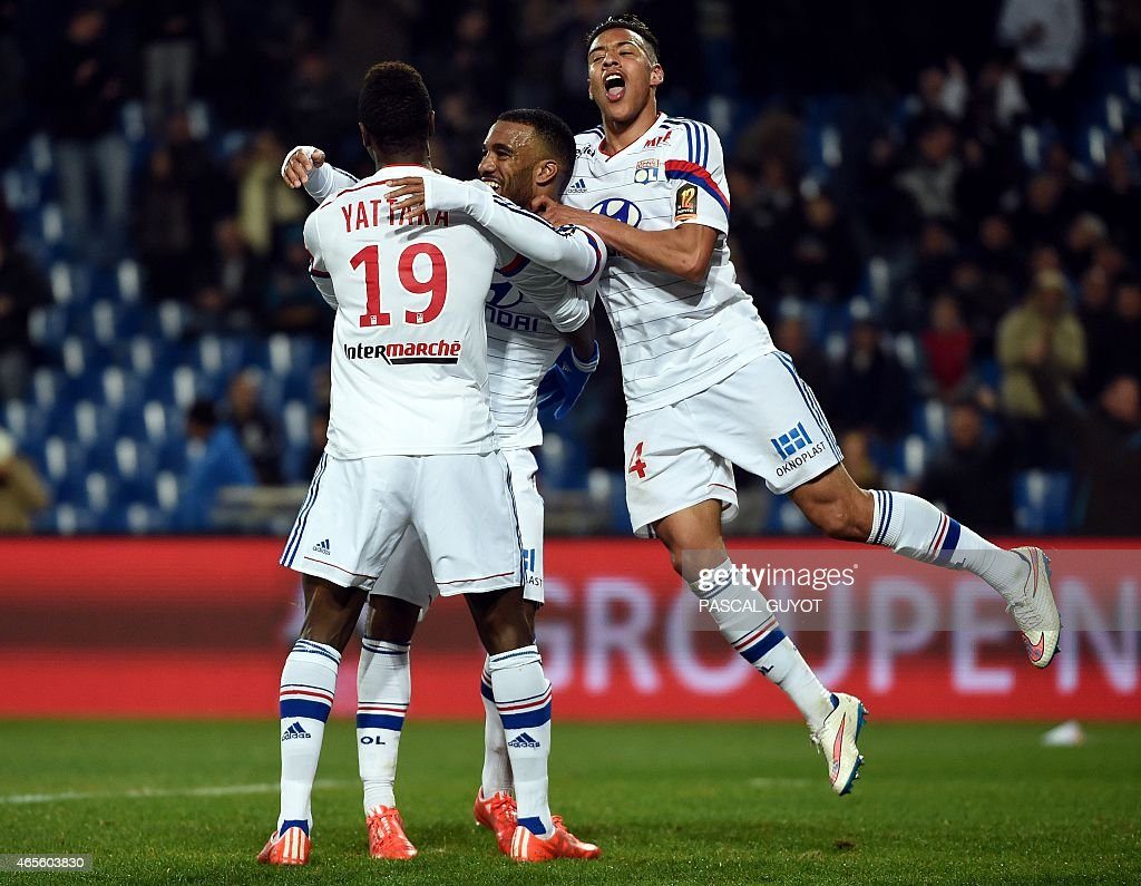 Lyon's French forward Alexandre Lacazette (C) is congratuled by his teamates after scoring a goal during the French L1 football match between Montpellier and Lyon, on March 8, 2015 at the La Mosson Stadium in Montpellier, southern France.