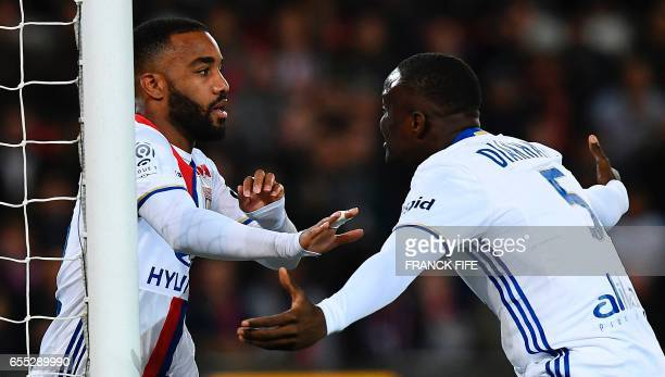 Lyon's French forward Alexandre Lacazette is congratuled by teammate Lyon's defender Mouctar Diakhaby after opening the scoring during the French L1...